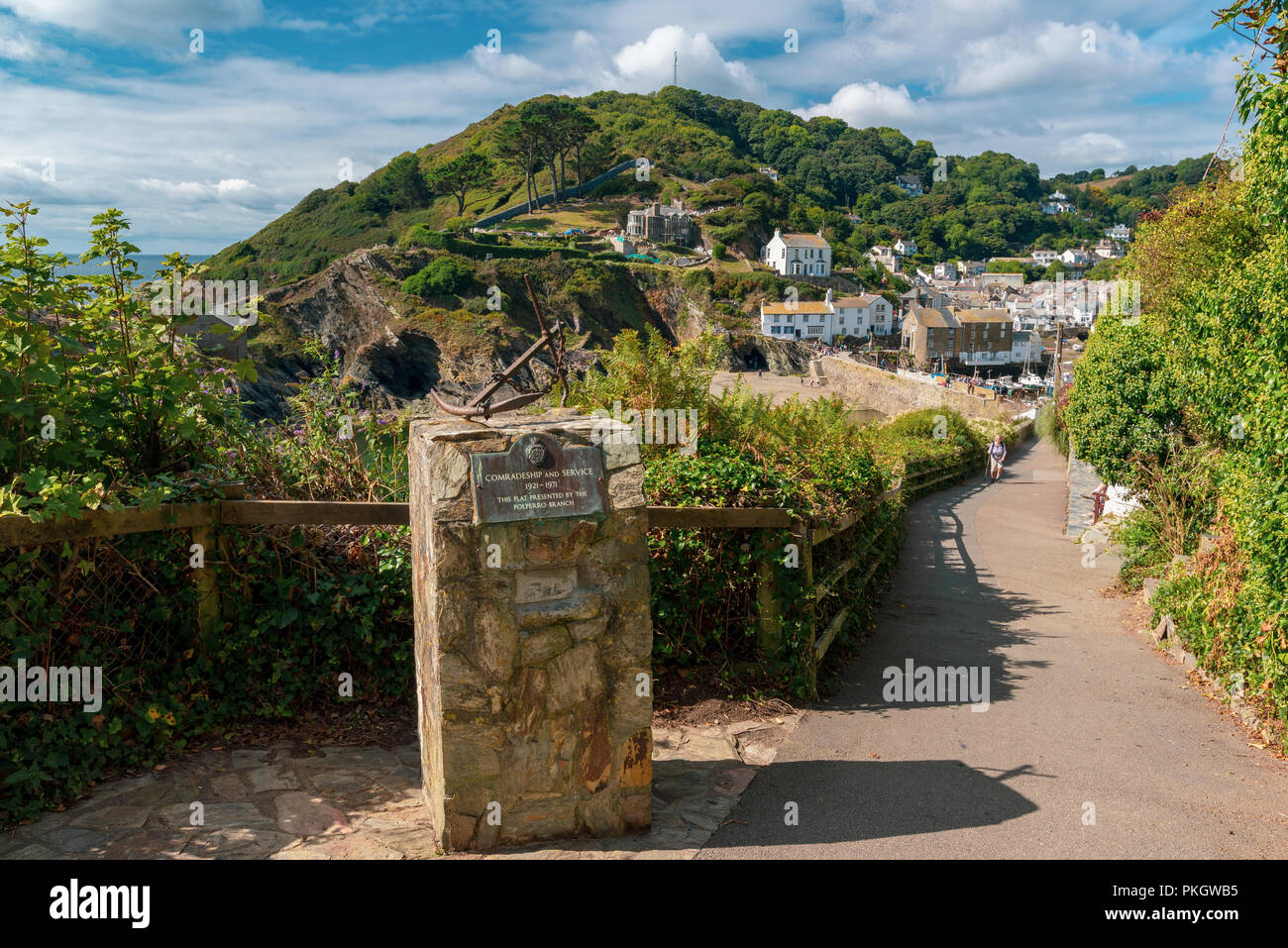 Engraved memorial stone and anchor above the the seaside village of  Polperro, South Cornwall, England, UK - Stock Image