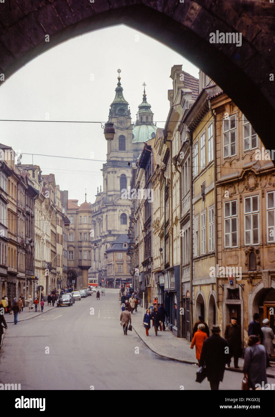 View of St Nicholas Church from underneath Lesser Town Bridge Tower in Prague, Czechoslovakia in April 1974. Original Archive Photo. - Stock Image
