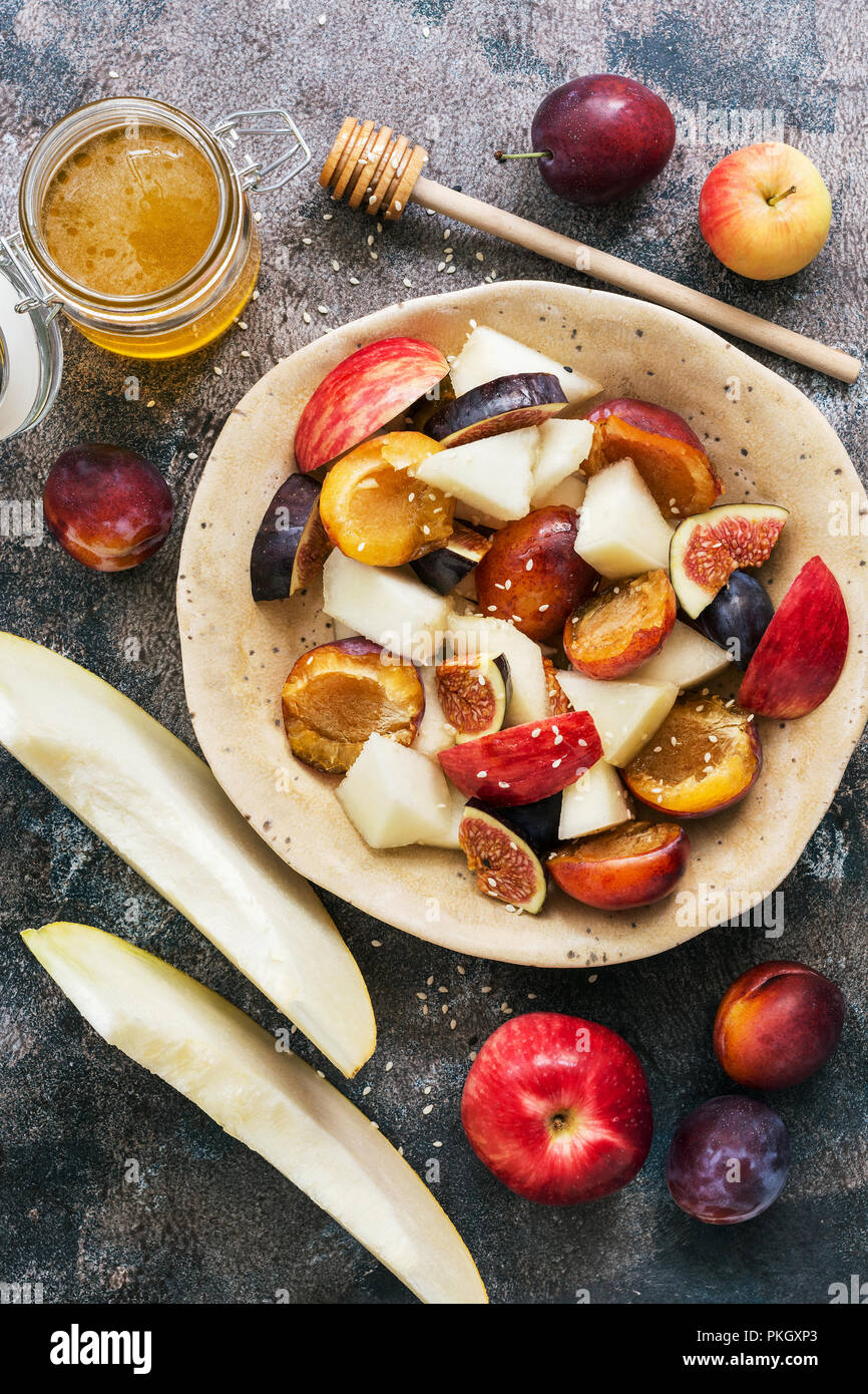 Fruit salad of melon, figs, apples and plums on a dark rustic background, top view. flat lay - Stock Image