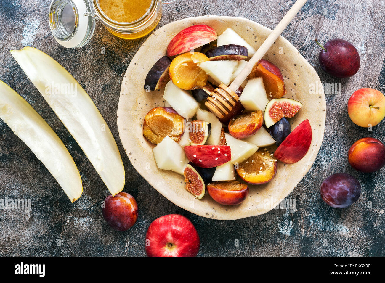 Fresh fruit salad of melon, figs, apples, plums and honey on a dark rustic background, top view. The concept of healthy eating. flat lay - Stock Image