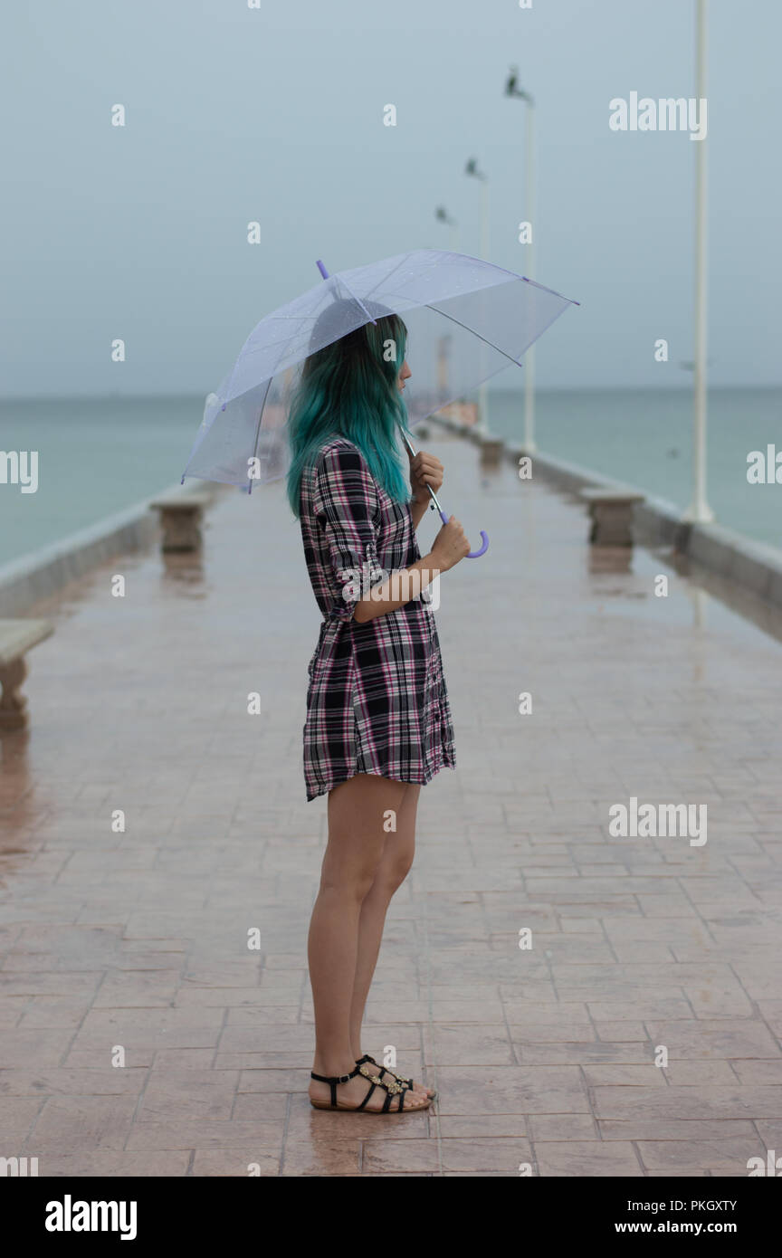 Nostalgic, melancholic girl on pier holding a transparent umbrella as light rain comes down.  Photo taken in Yucatan, Mexico. - Stock Image