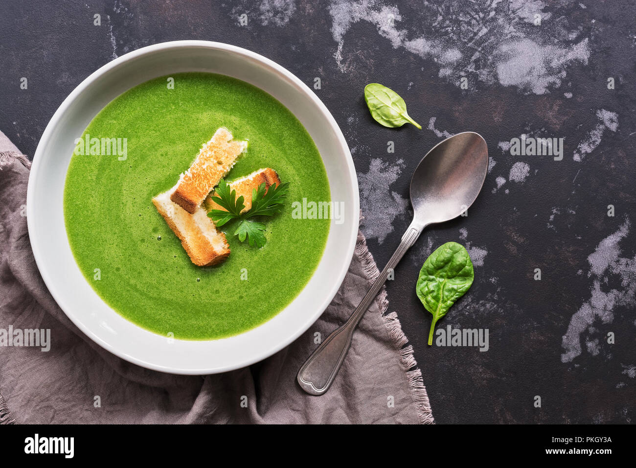 Green vegetable cream soup with spinach on a dark concrete background. Dietary healthy lunch or dinner. Top view, copy space. Stock Photo