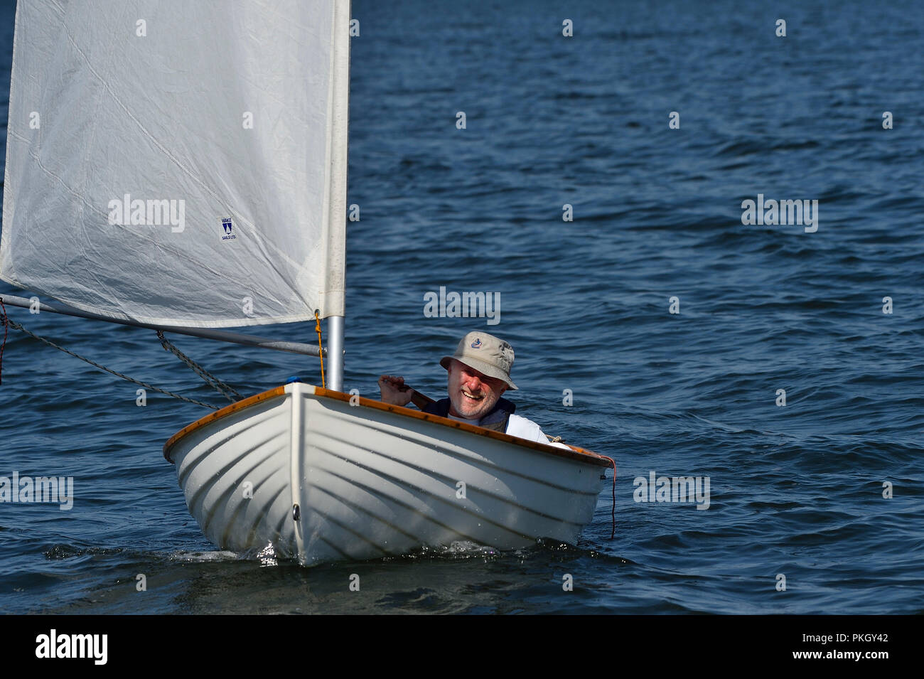 A small sail boat sailing on the water in the Strait of Georgia near Vancouver Island British Columbia Canada - Stock Image