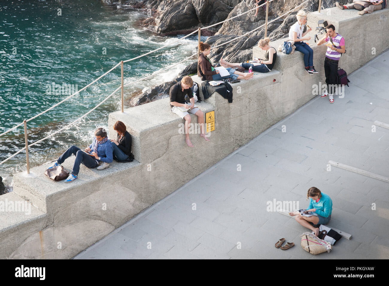 CINQUE TERRE, ITALY - APRIL 25 2011; Young adults travelers relaxing by sea sitting around checking plans, writing diaries or letters and relaxim - Stock Image