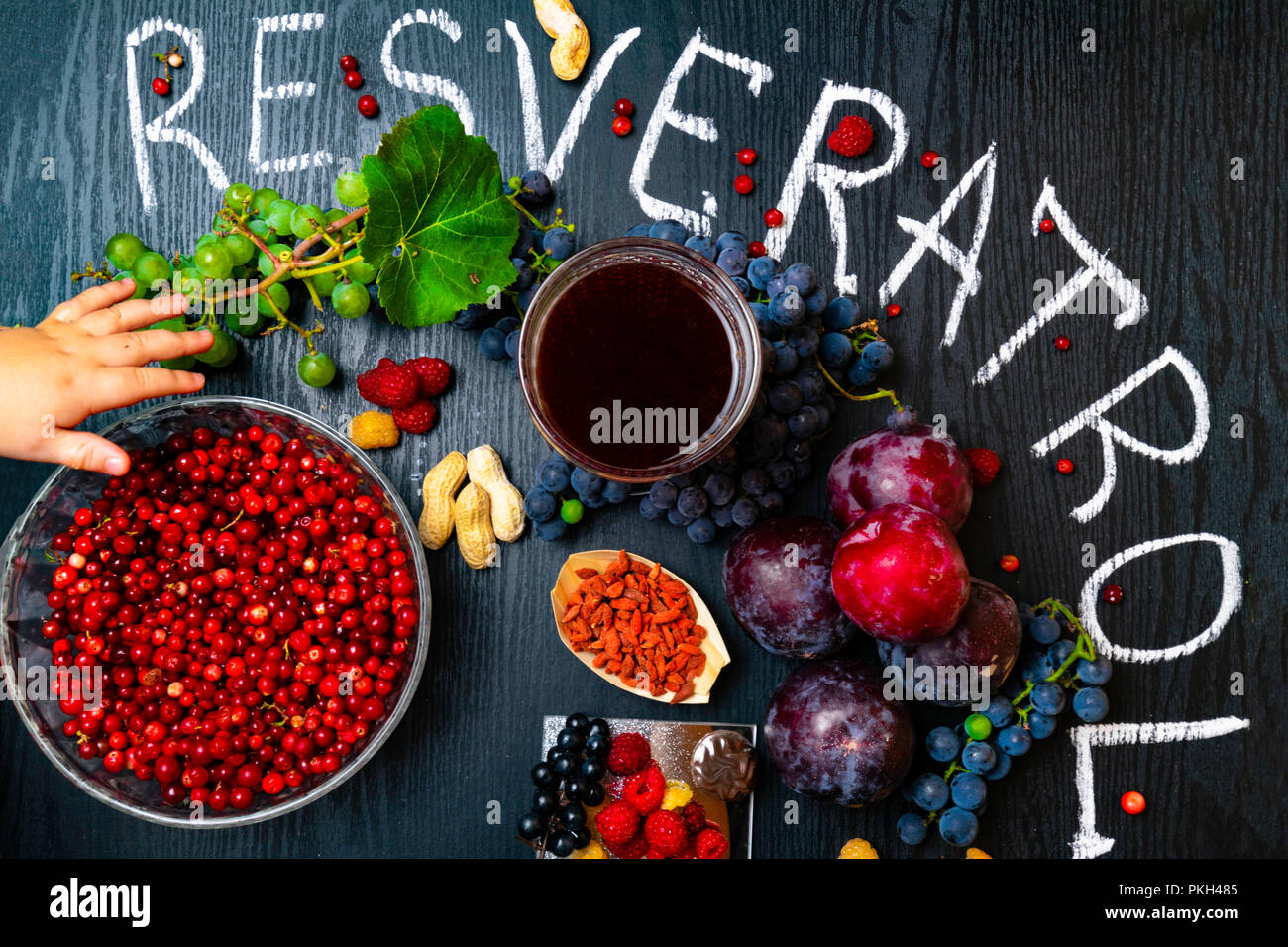 Food Rich With Resveratrol Grapes Plums Goji Peanuts Cranberry Raspberrys Dark Chocolate Red Wine On Black Wooden Background Stock Photo Alamy