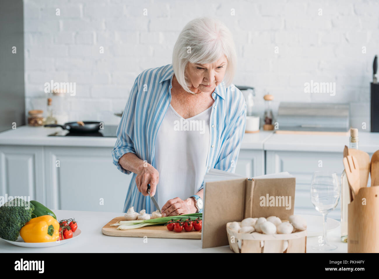 portrait of senior lady looking for recipe in cookery book while cooking dinner at counter in kitchen - Stock Image