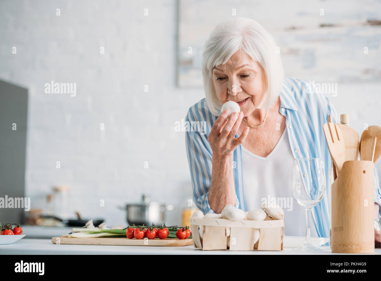 portrait of grey hair lady checking mushrooms while cooking dinner at counter in kitchen - Stock Image