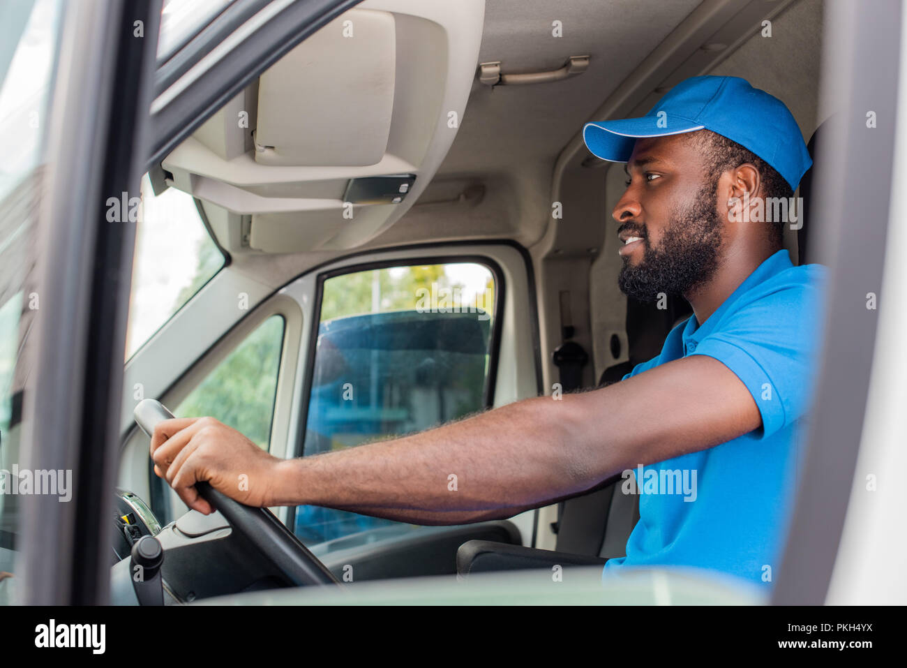 side view of african american delivery man driving van - Stock Image