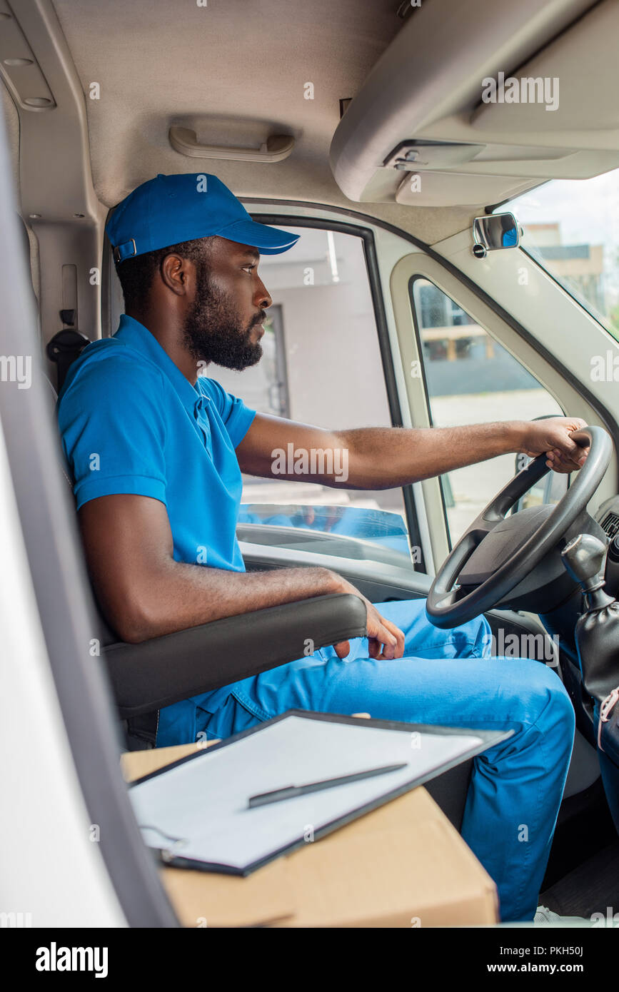 african american delivery man driving van - Stock Image