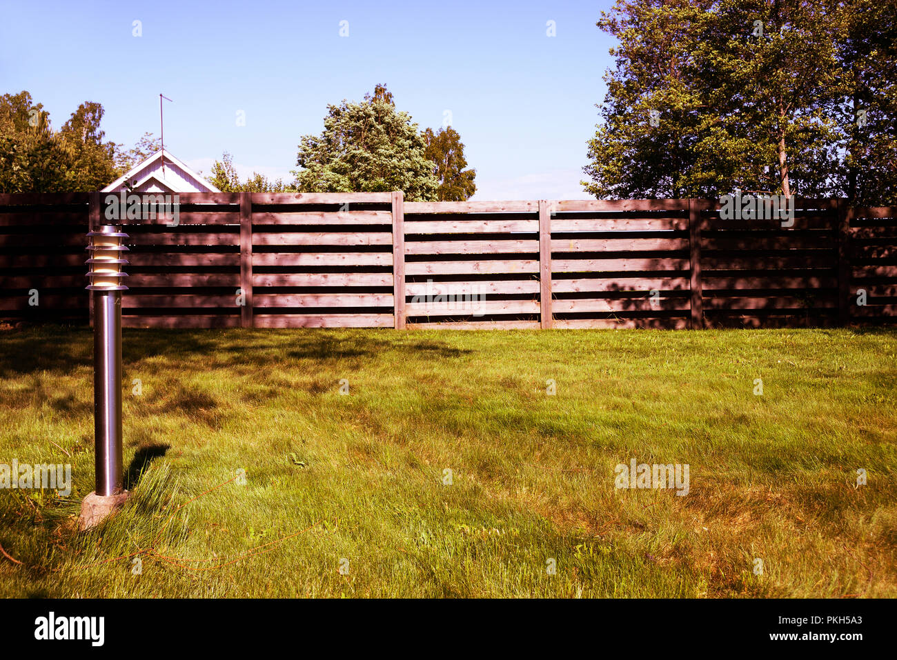 lantern, green lawn and fence, photo filter, deadpan - Stock Image