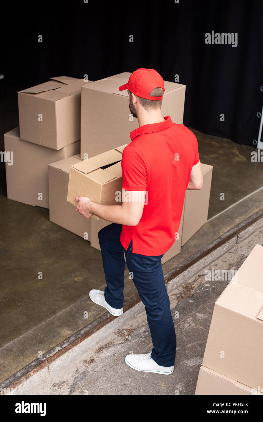 high angel view of young delivery man in red uniform discharging cargo - Stock Image