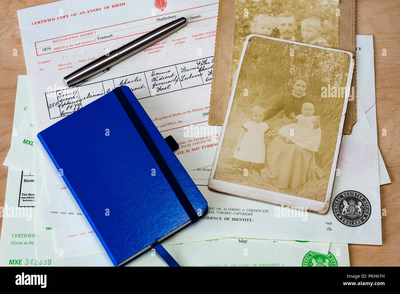 Collection of birth, marriage, death certificates & a notebook with some old photographs used for family history research, England, UK Stock Photo
