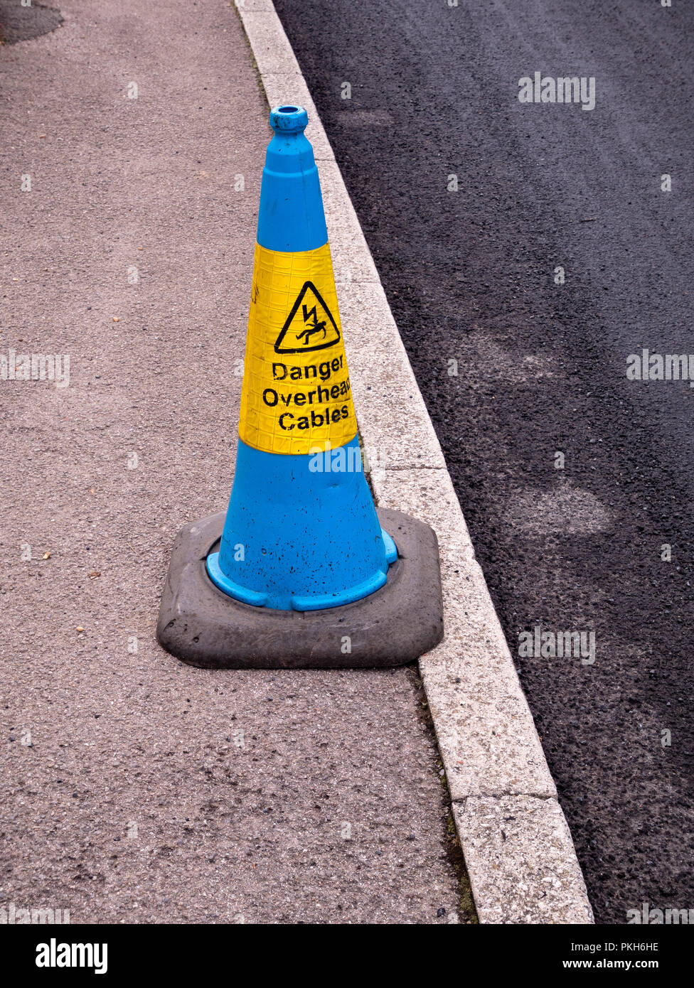 A blue traffic cone warning of overhead cables - Stock Image