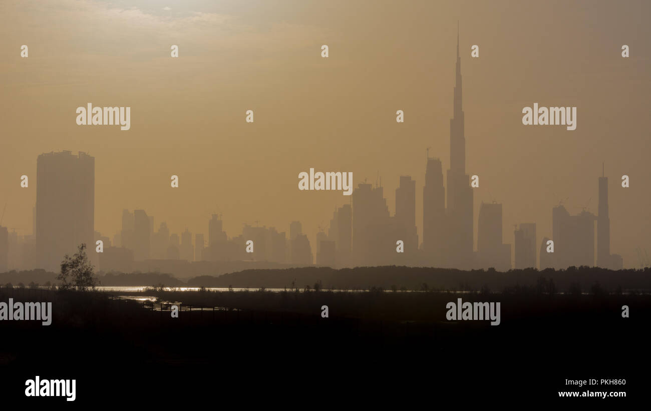 The fast paced city of Dubai in the United Arab Emirates is fascinating and seeing the hazy sunset skyline from the peaceful Ras al Khor is a treat. - Stock Image