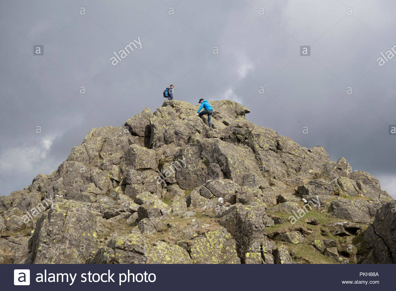Scrambling on the summit of Dow Crag in the Coniston Fells in the English Lake District. - Stock Image