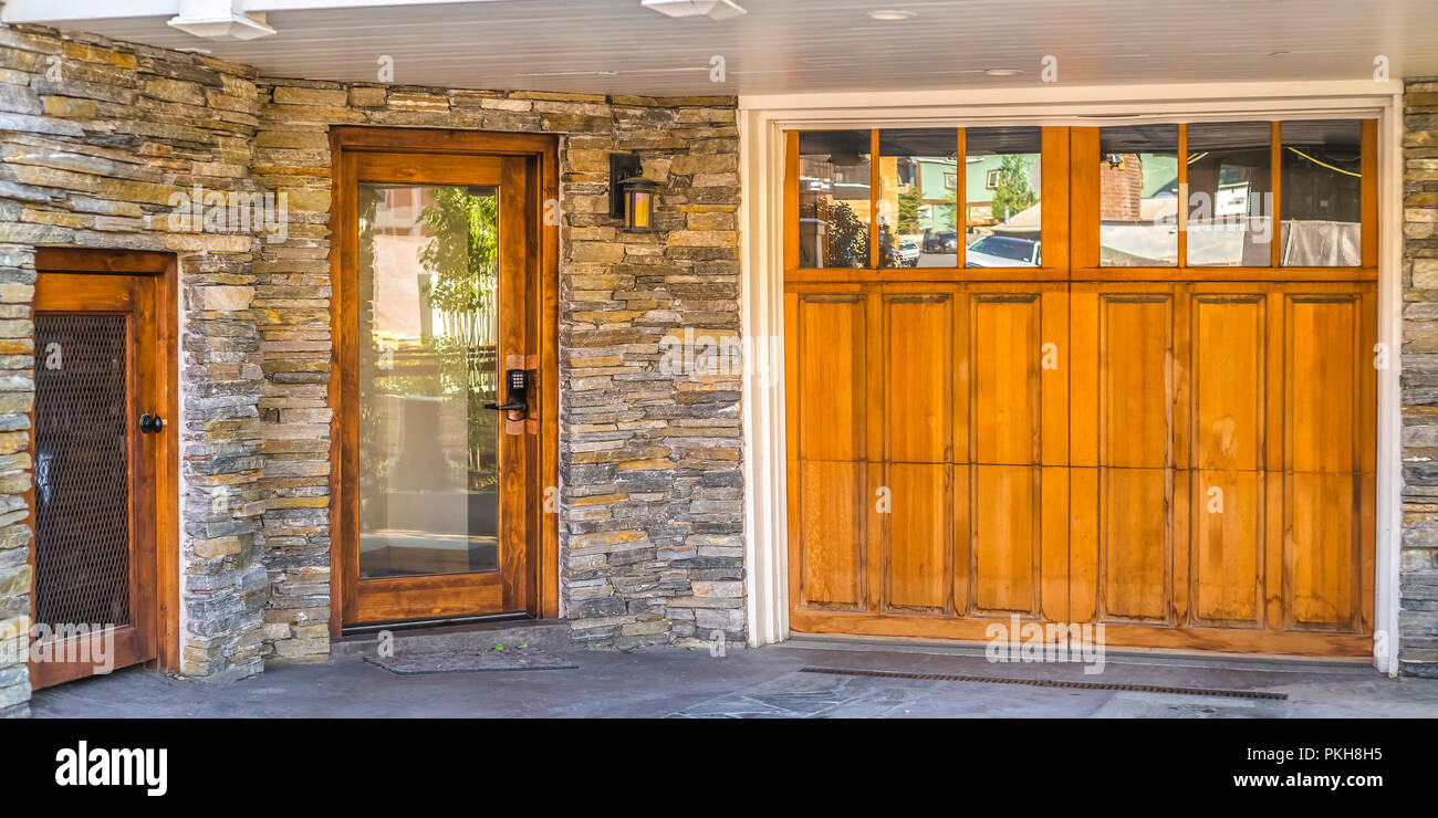 Stone Brick Entry With Wood Garage Front Door Pano Stock Photo