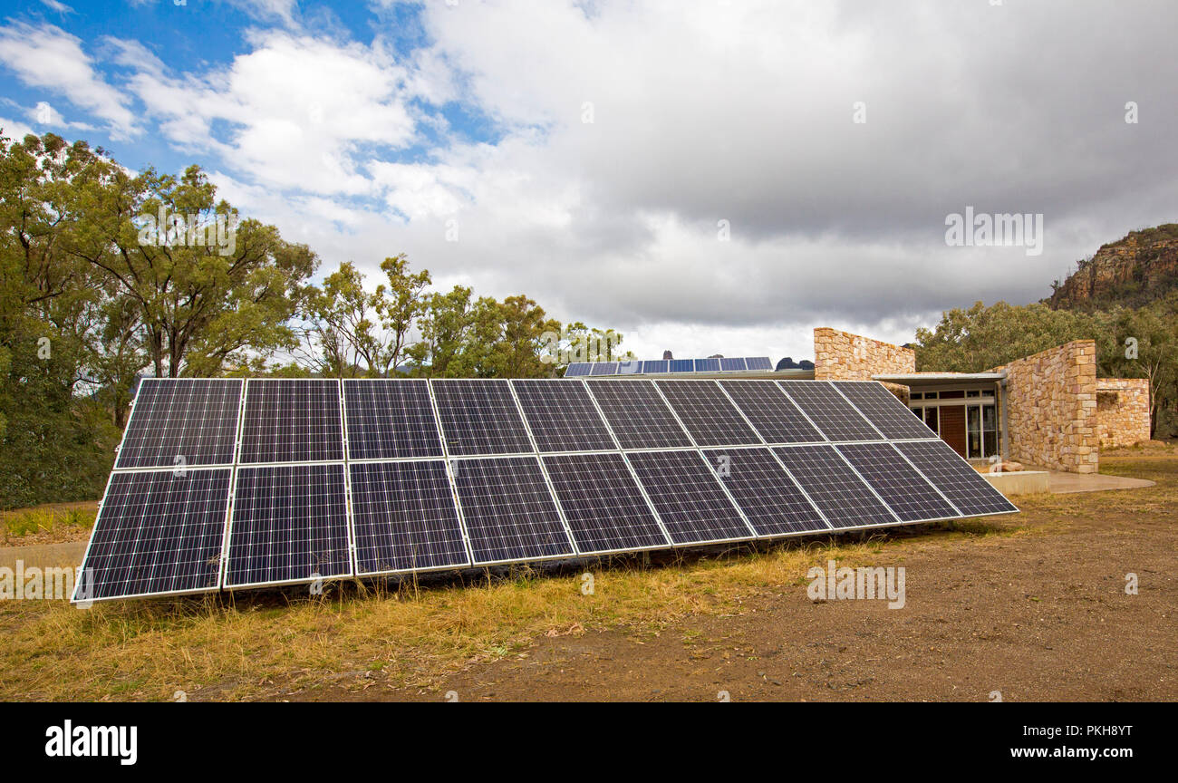 Large array of solar panels beside modern stone building in rural area of NSW Australia - Stock Image