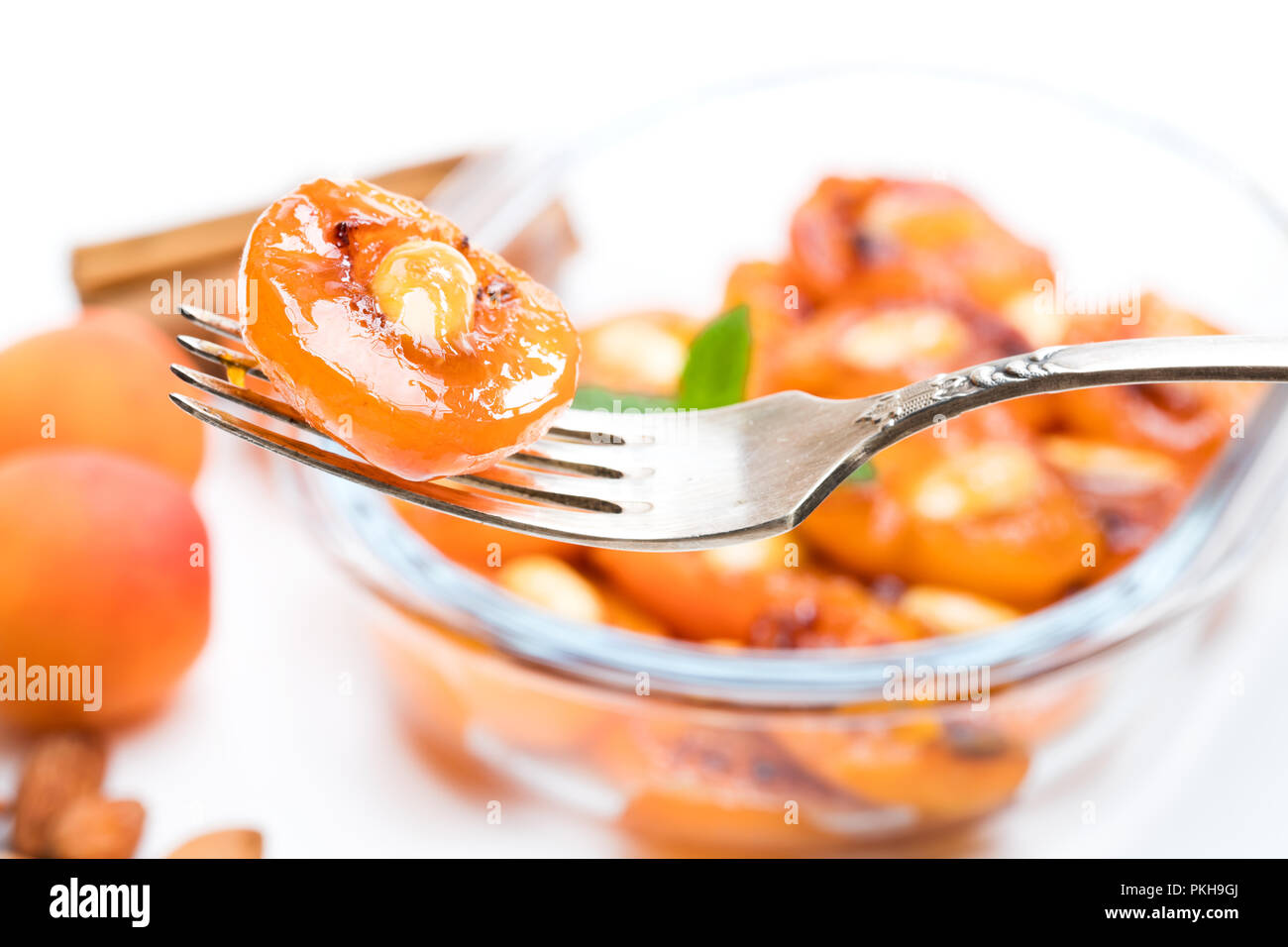 Caramelized  apricots with almonds isolated on white - Stock Image