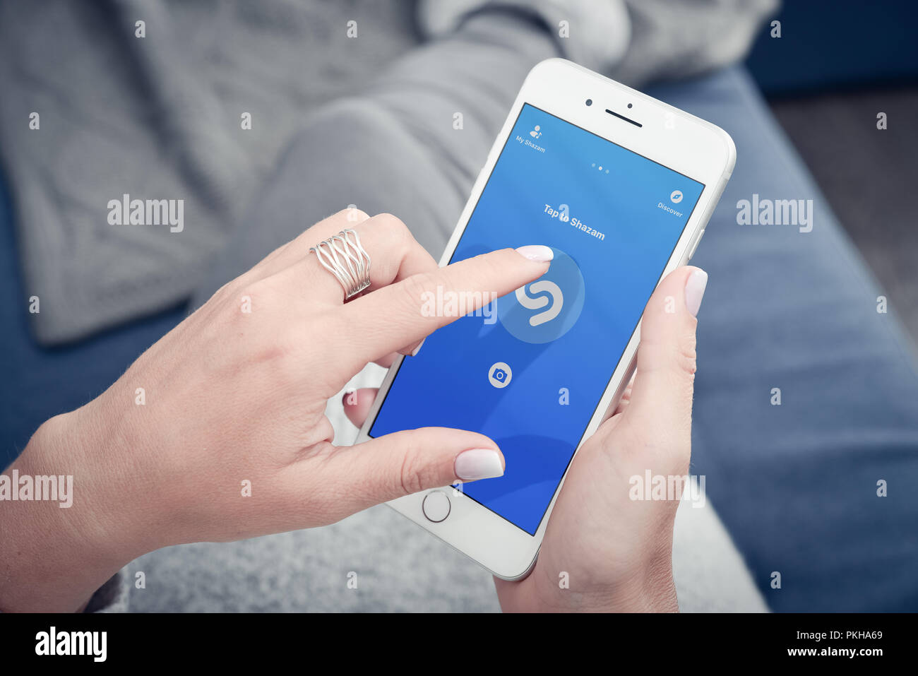 Kyiv, Ukraine - January 24, 2018:  Woman hands using Shazam application on Apple Iphone 8 plus for searching music what she like while lying at home o Stock Photo