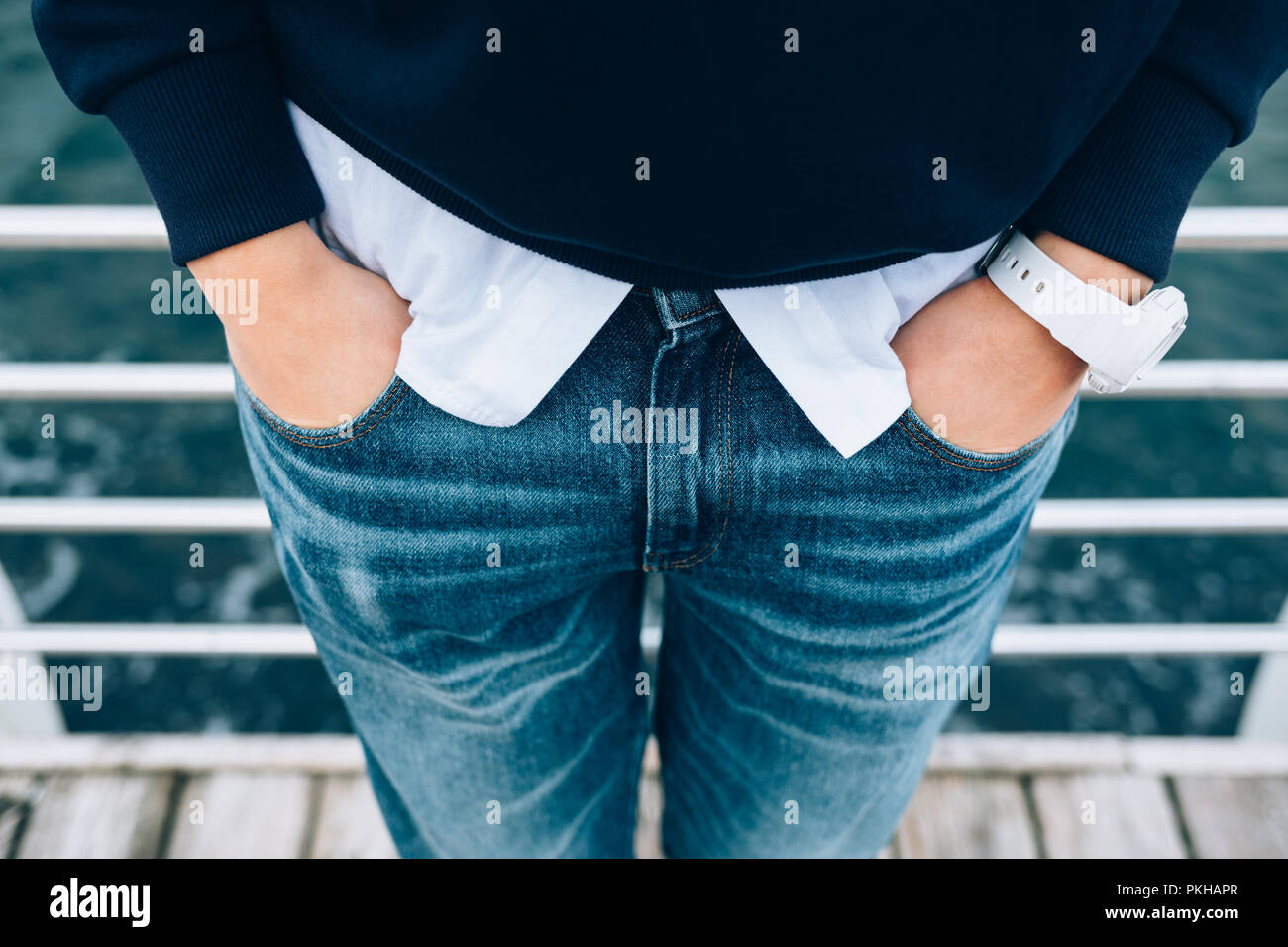 Candid lifestyle close-up of fashionable female wearing wristwatches holding hands in pockets of classic jeans standing on embankment near sea. Detail - Stock Image