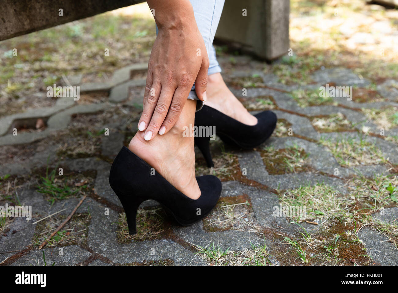 Woman Removing High Heels Touching Her Ankle - Stock Image