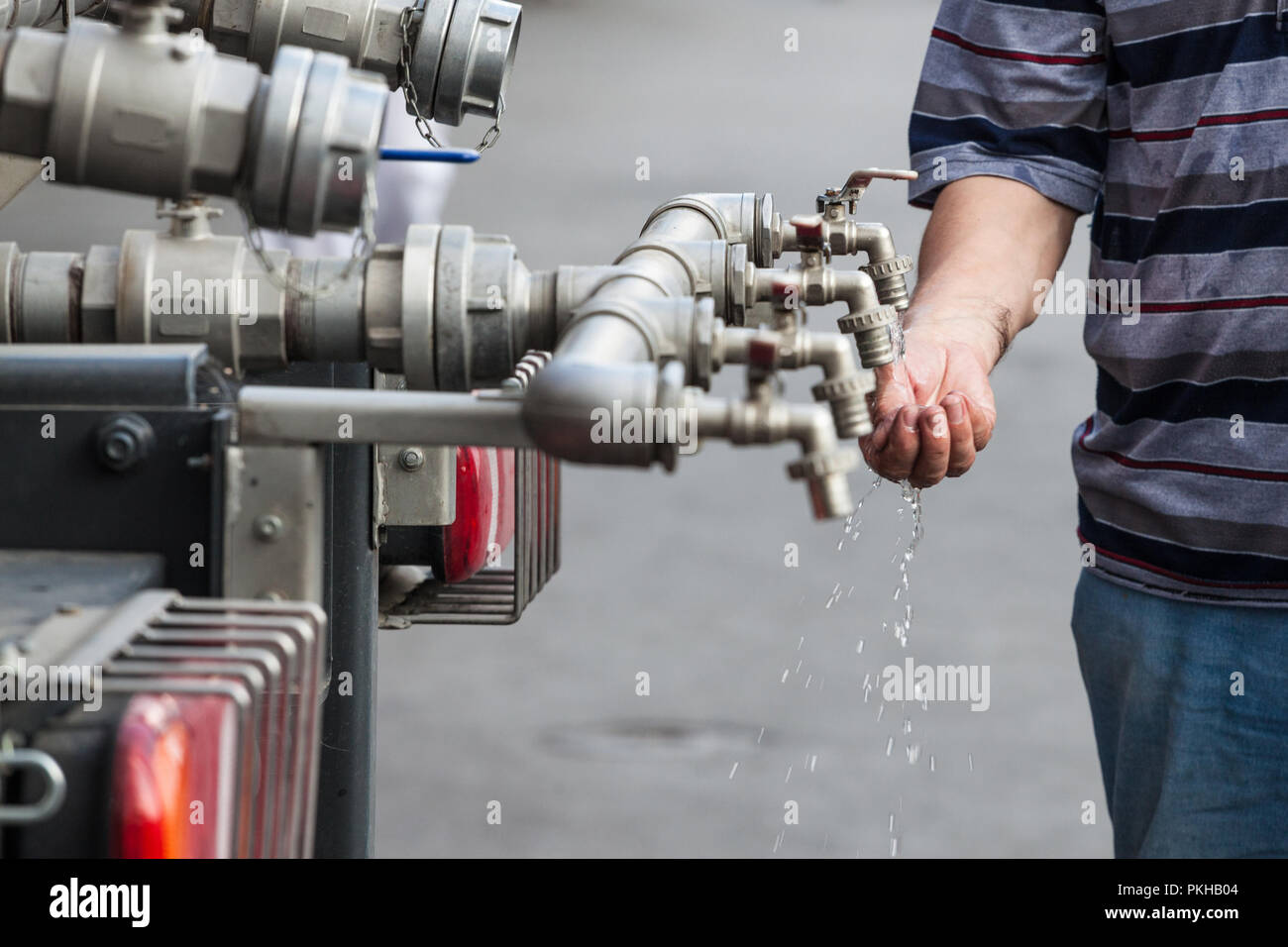 Water tap made of several pipes, with hands trying to hold water to save it and drink it. This faucet distributes to public a clean drinking water  Pi - Stock Image