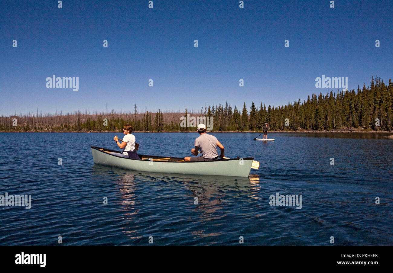 A middle aged married couple paddling a canoe on Waldo Lake, a volcanic caldera lake in the central Oregon Cascades near the town of Oakridge. - Stock Image