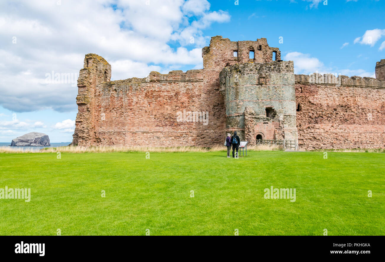 Couple reading information board at 14th century fortified Tantallon Castle, North Berwick, East Lothian, Scotland, UK - Stock Image