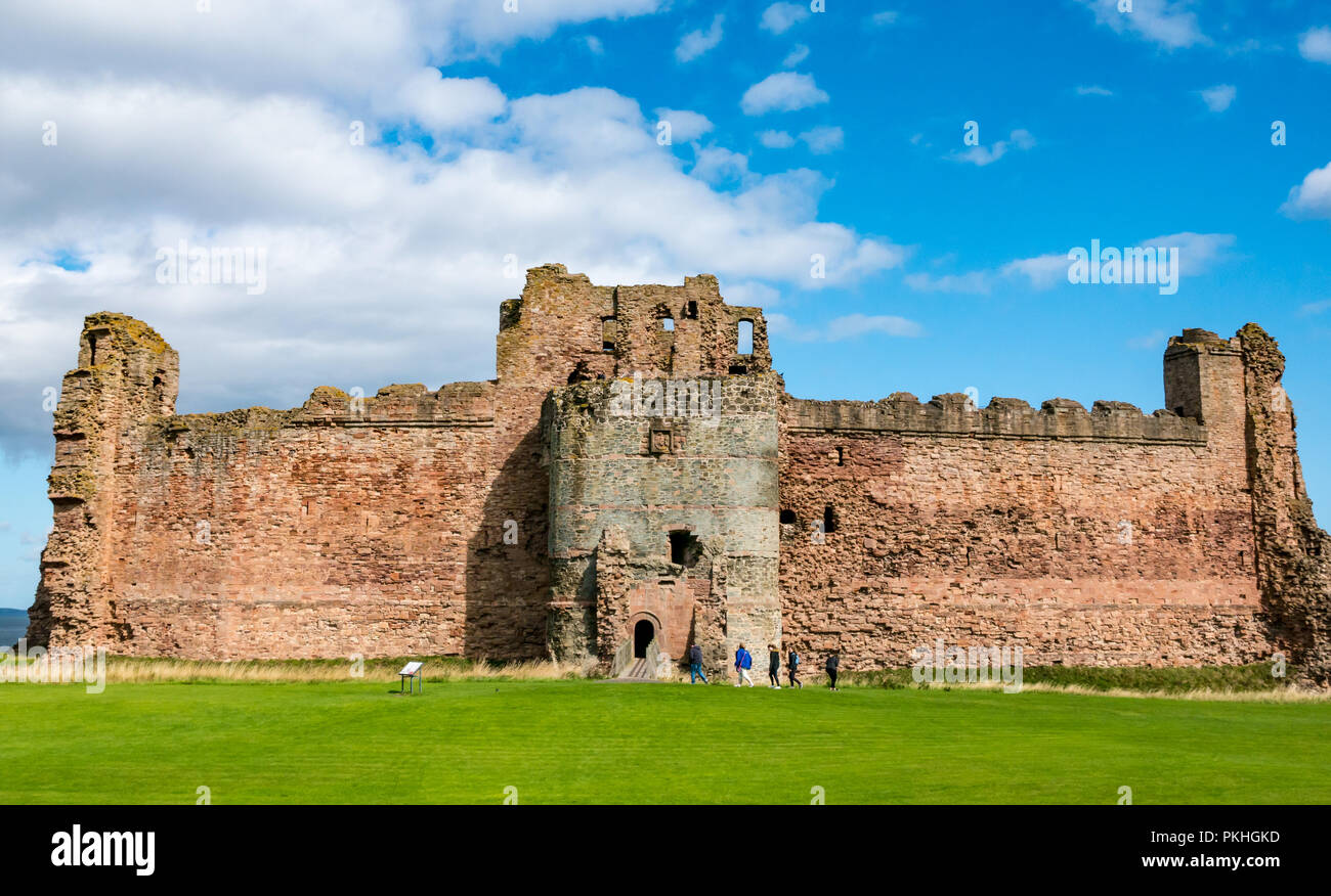 Group of people going into 14th century curtain wall fortified Tantallon Castle, North Berwick, East Lothian, Scotland, UK - Stock Image