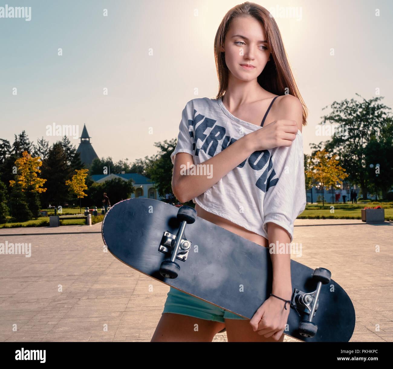 Long haired girl holding skateboard posing with bare shoulder - Stock Image