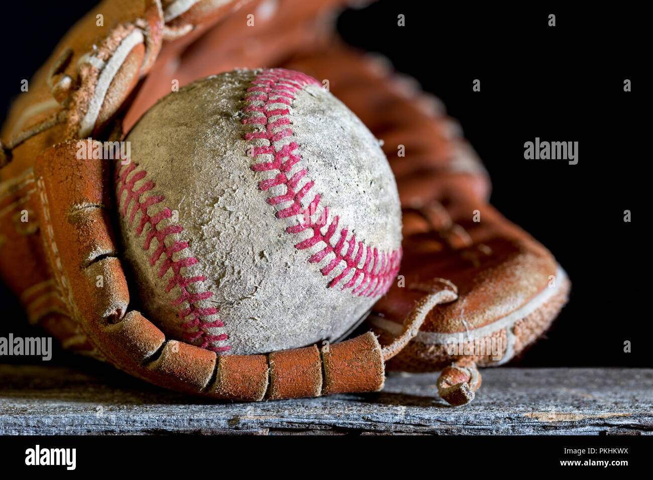 Baseball glove and ball on weathered wood bench. Close up with selective focus on the scuffed up texture detail. Copy space in the black background. - Stock Image