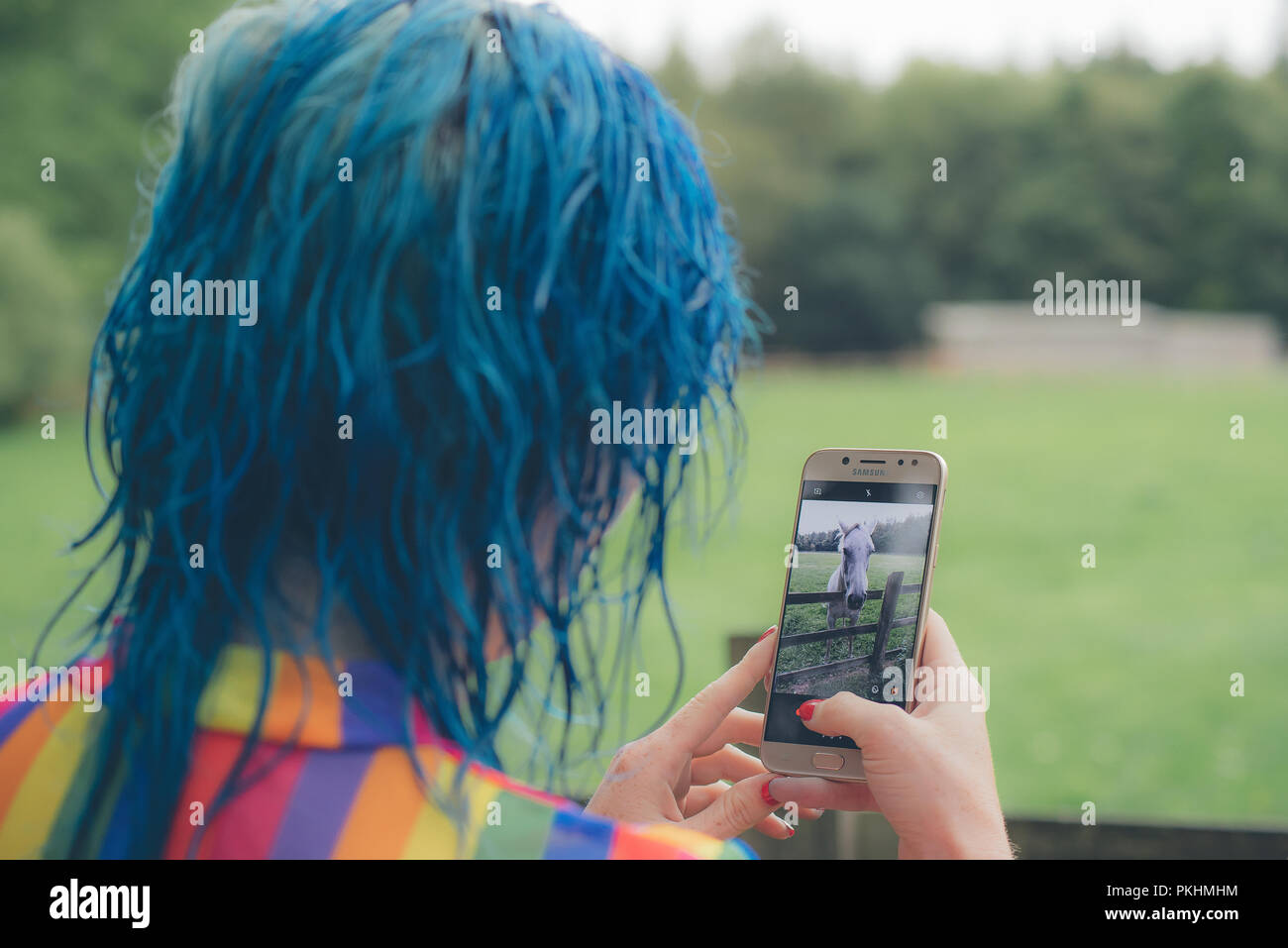 5b59b86c09c6d A blue haired woman, wearing a gay pride like top, takes a picture of