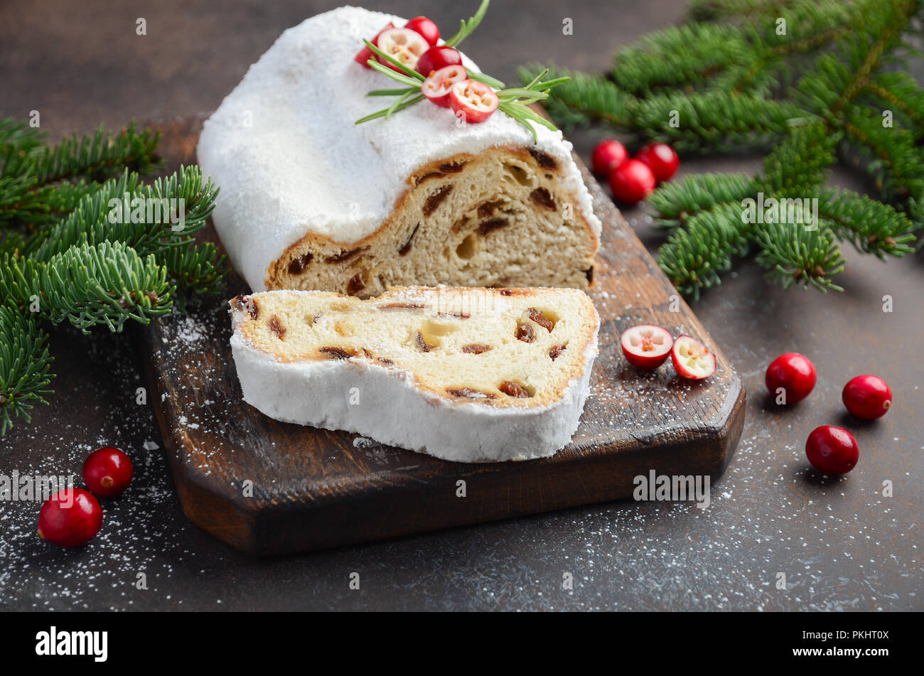 Christmas Stollen. Traditional German, European Festive Dessert. Holiday Concept Decorated with Fir Branches and Cranberries. - Stock Image