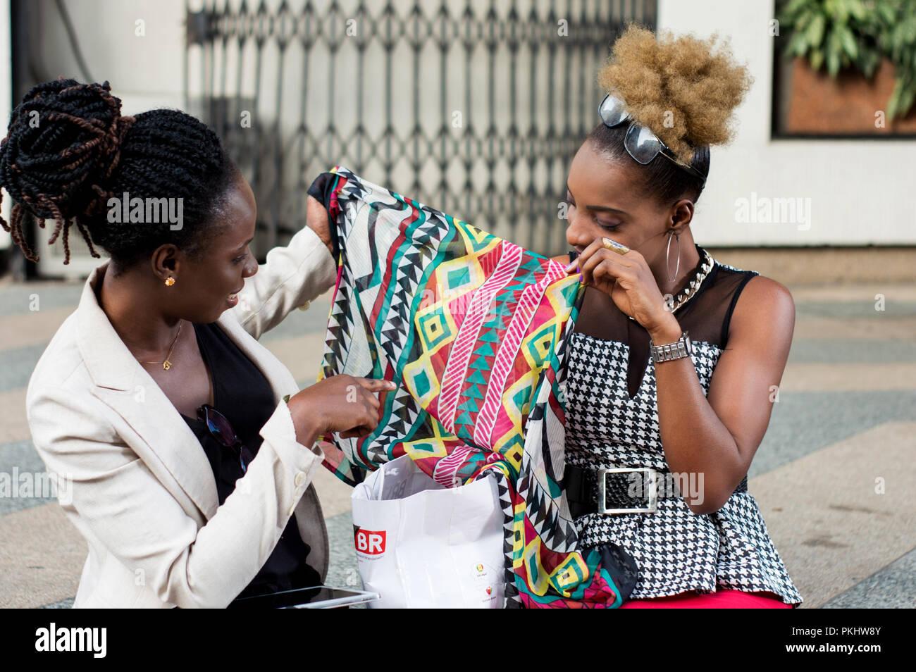 Two smiling businesswomen watching the scarf bought at the shop. - Stock Image