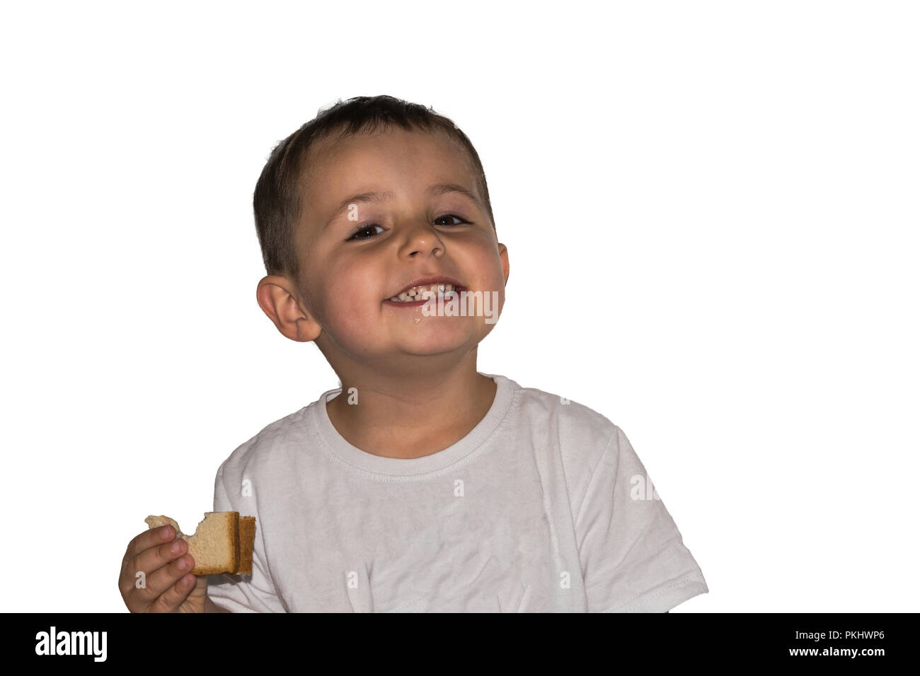 Little laughing boy with toast in hand is standing in front of a white background. - Stock Image