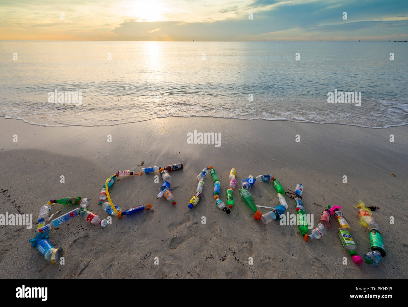 MIAMI - CIRCA JUNE, 2018: 'ACT NOW' spelled out in the sand using plastic trash collected on Miami beach, a reminder to reduce, reuse, recycle - Stock Image