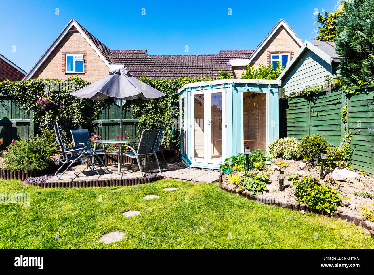 English garden, summer house, patio set, table and chairs outside, fenced garden, stepping stones, umbrella over table, summer houses, UK, England, - Stock Image