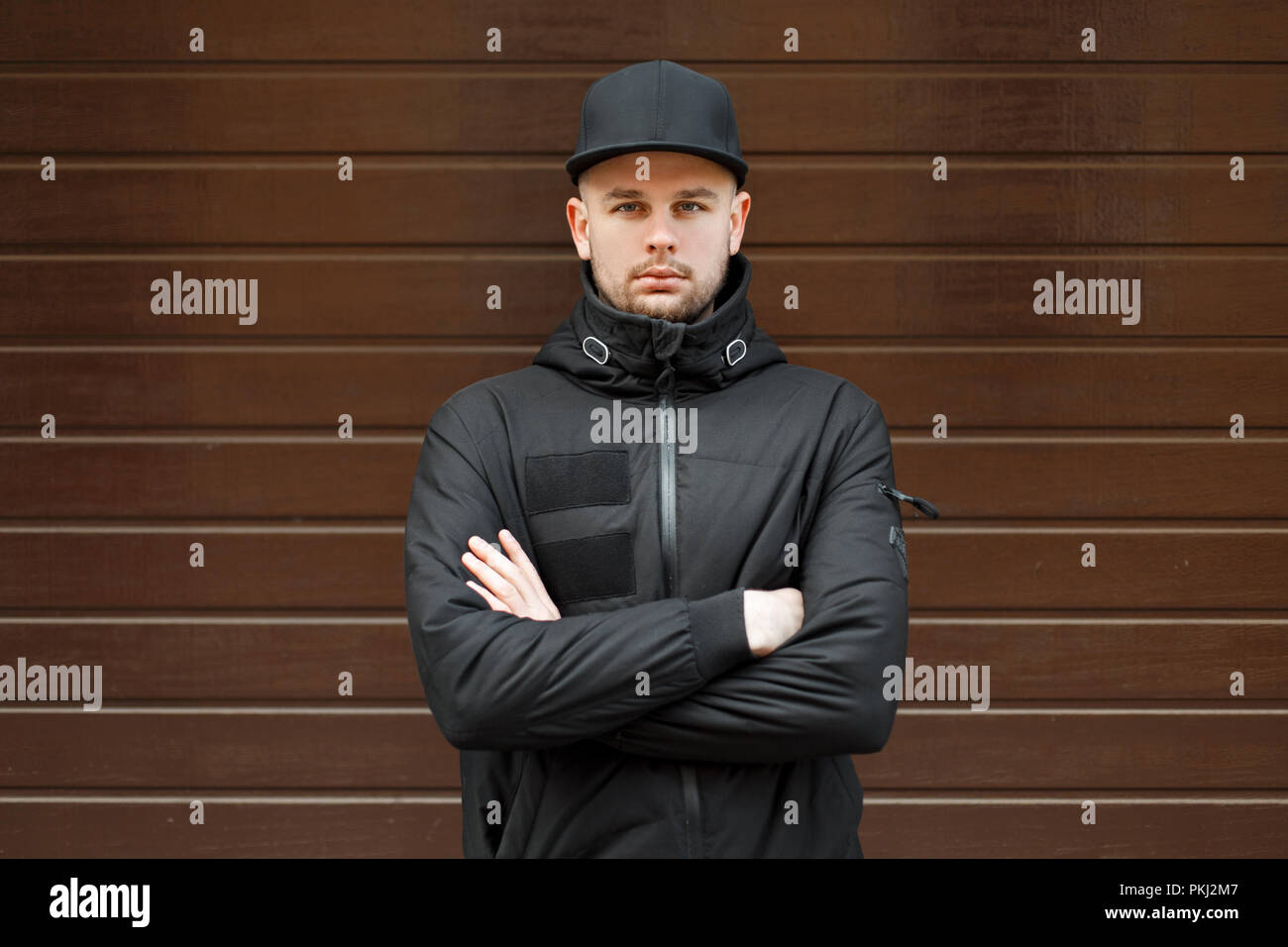 31452b5e6cf stylish handsome man in a black fashionable baseball cap and black winter  jacket stands and looks