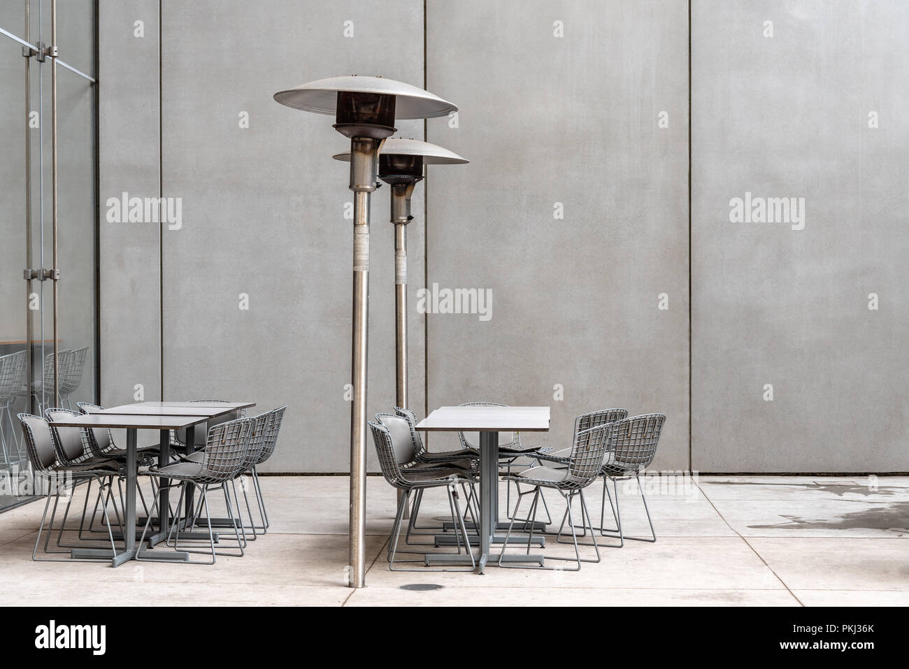 Modern restaurant terrace with tables, chairs and heaters against concrete wall with space for copy with no people. New York City, USA - Stock Image