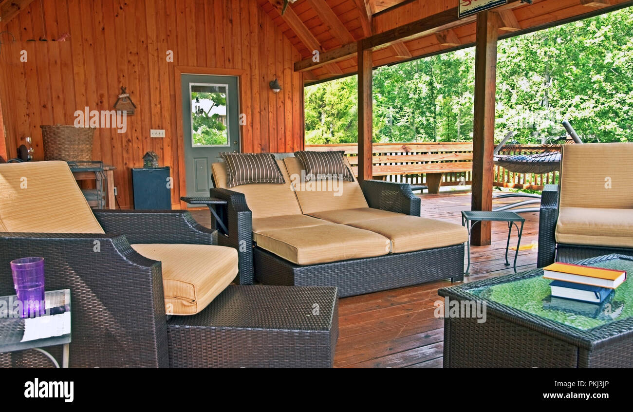 An outdoor deck area furnished with comfortable seating for hours of leisure living. - Stock Image