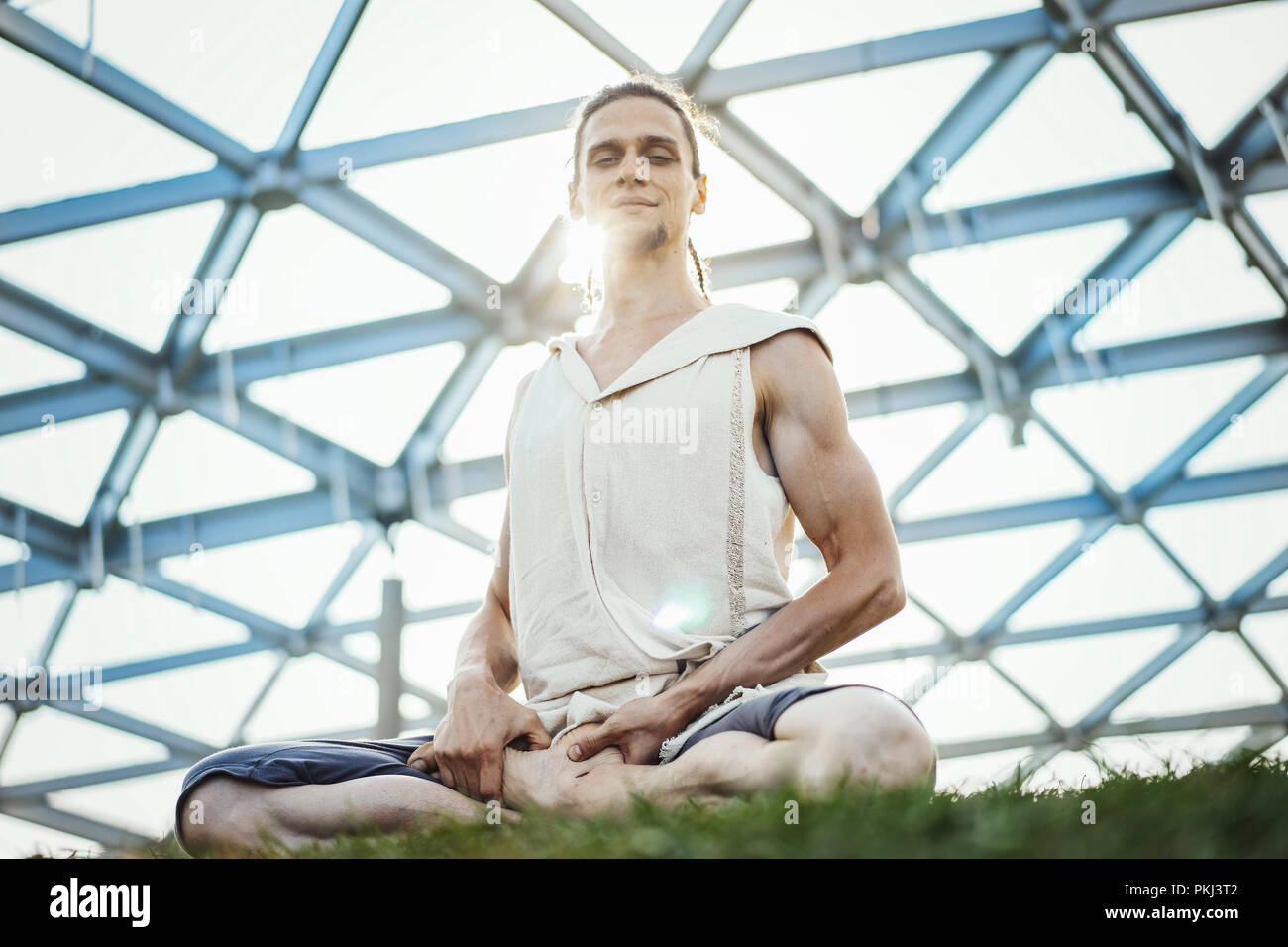 Close up of attractive athletic man practicing yoga and warming up outdoors. - Stock Image