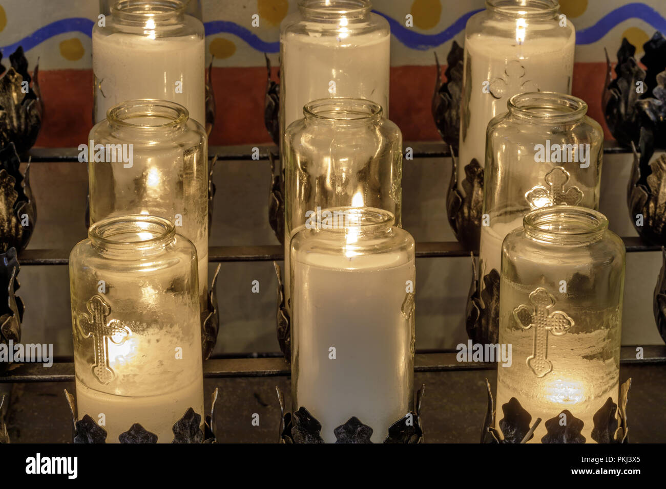 Burning votive candles in a church. - Stock Image