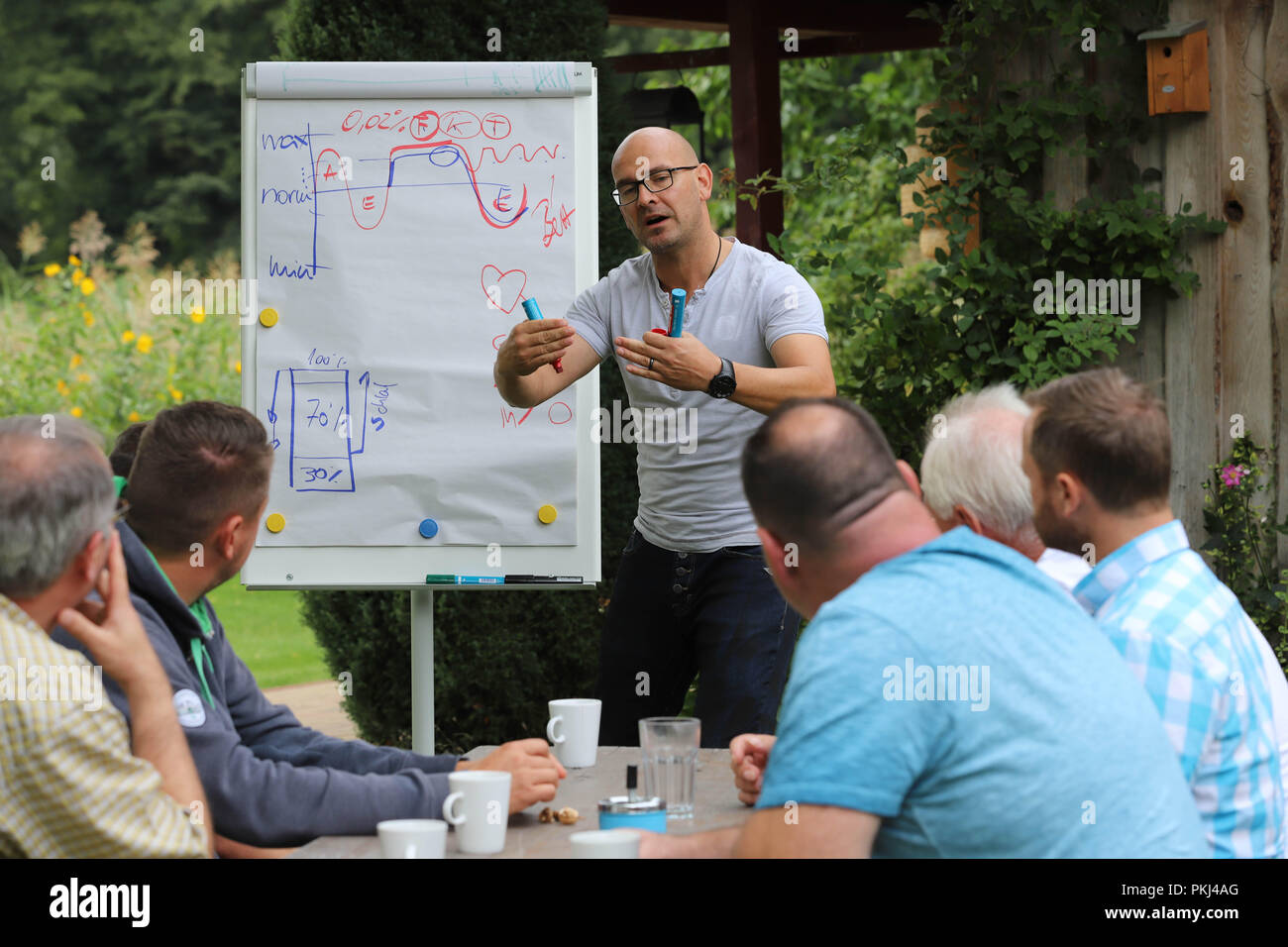 Behavioral trainer during a lecture on 'stress management' in a summery garden in Brandenburg / Germany. - Stock Image