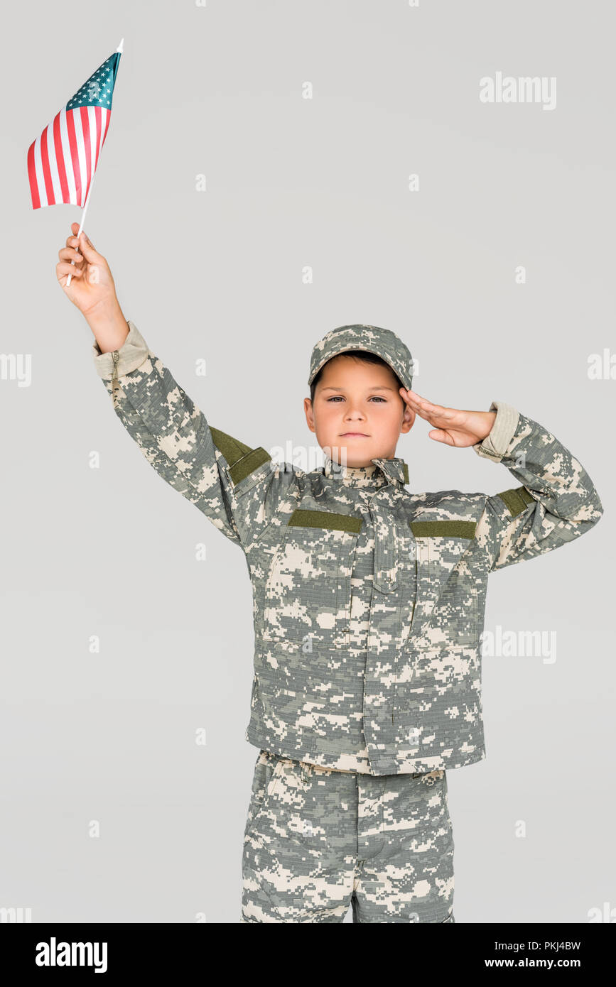 portrait of boy in camouflage clothing saluting while holding american flagpole in hand isolated on grey Stock Photo
