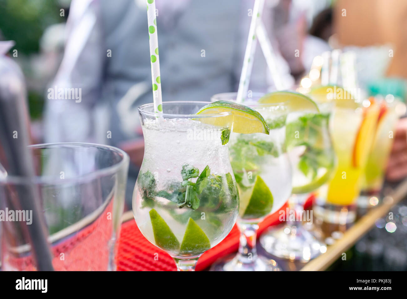 Bartender makes cocktail mojito. Misted glass, selective focus. Alcoholic beverage based on bar counter with ice cubes and lyme. outdoor party - Stock Image