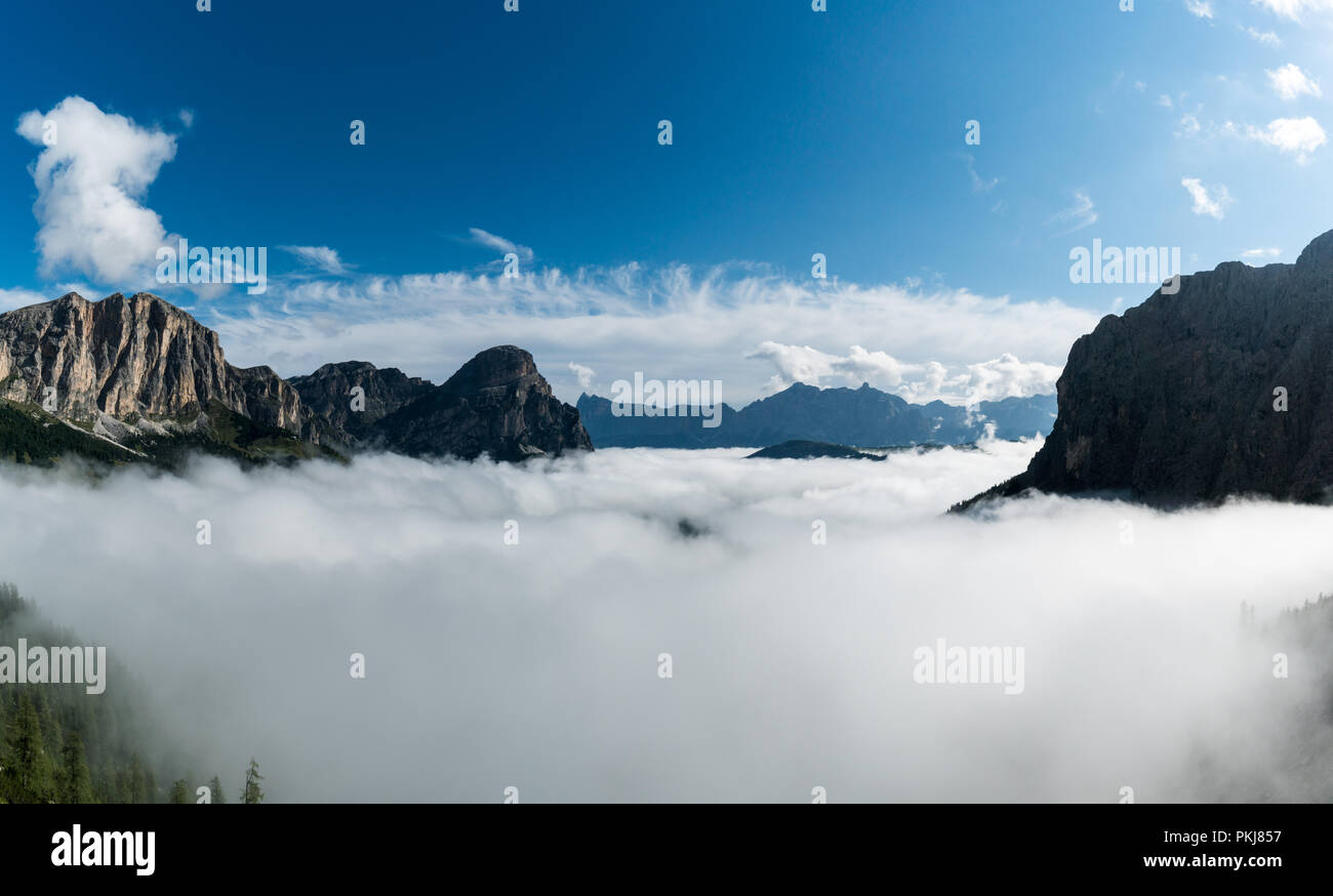 panorama mountain landscape in the Val Gardena in the Italian Dolomites with mountain peaks and thick cloud cover in the valleys underneath a blue sky - Stock Image