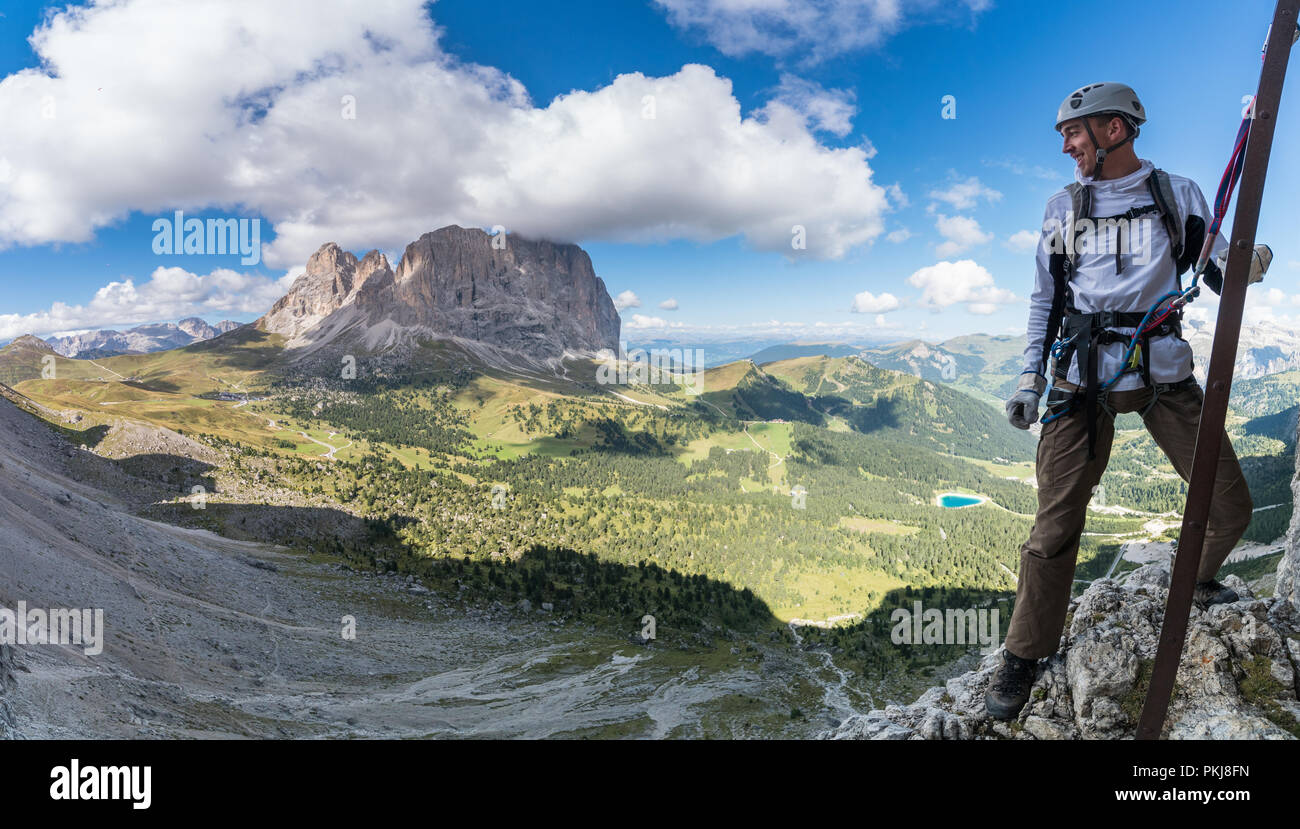 young attractive male mountain climber in the Dolomites of italy with a great panorama view of the Langkofel and Passo Sella Stock Photo