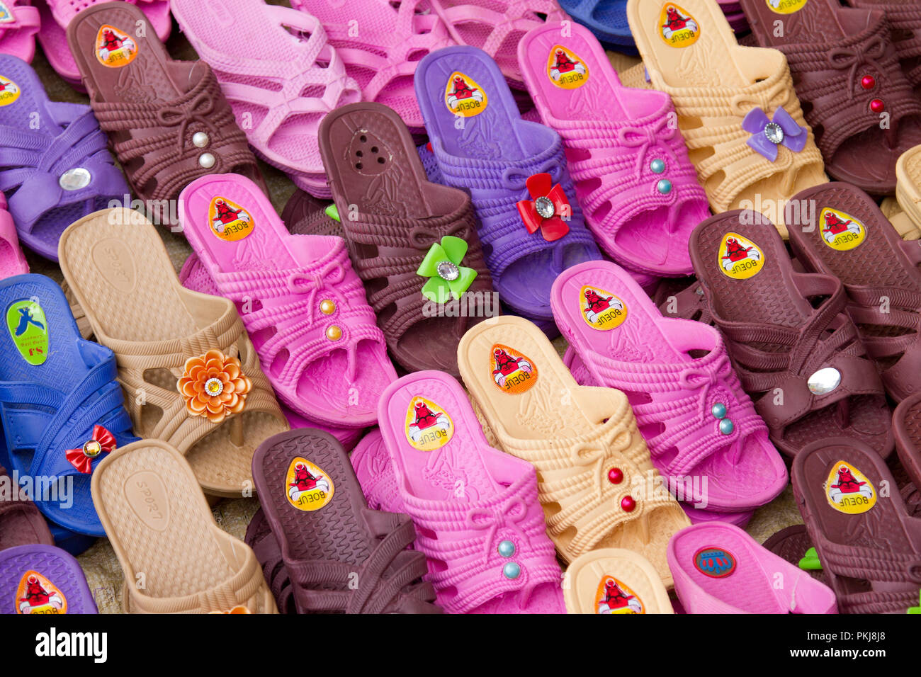 Group of colourful plastic shoes for sale at Madagascan farmers market,Madagascar,africa - Stock Image