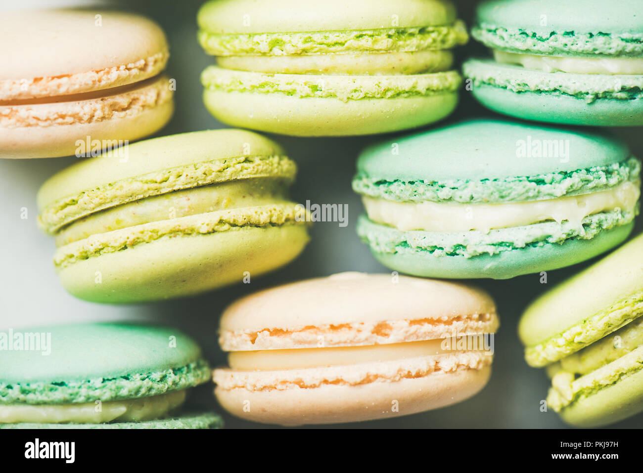 Pastel colored French macaroons cookies over light background - Stock Image
