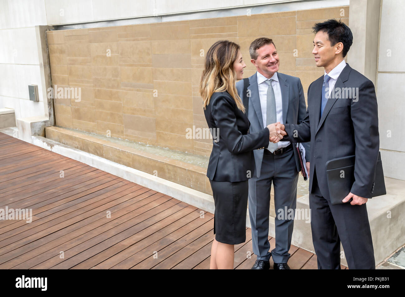 A group of executives shaking hands in their office building - Stock Image